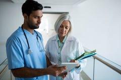 Doctors discussing over digital tablet in corridor Stock Photos