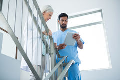 Doctors discussing over digital tablet while standing on stairs Royalty Free Stock Photo
