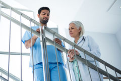 Doctors discussing over digital tablet while standing on stairs Stock Photography