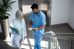 Doctors discussing over digital tablet while walking on stairs Stock Photos