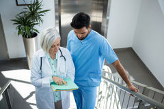 Doctors discussing over report while standing on stairs Royalty Free Stock Photos