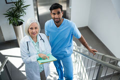 Doctors discussing over report while standing on stairs Stock Images