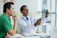 Doctors discussing x-ray. Of patient with compound fracture royalty free stock photos