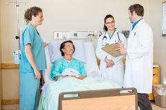 Doctors Discussing Report While Nurse And Patient Stock Photos