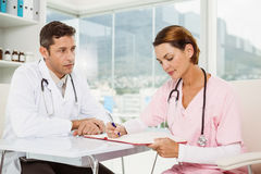 Doctors discussing reports at medical office Stock Photography