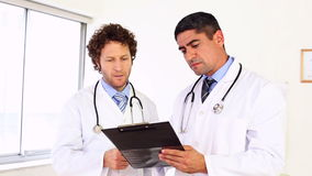 Doctors discussing something on clipboard stock video footage