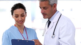 Doctors discussing together. While pointing at a notepad stock footage