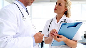 Doctors discussing and writing on a folder. In meeting room stock footage