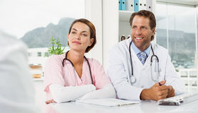 Doctors in discussion with patient in medical office Stock Image