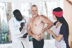 Doctors examine an elderly man who has a backache in his back. Doctors examine an elderly men who has a backache in his back. He was engaged in gymnastics. They Stock Images