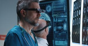 Doctors examining brain scan with VR headset. Medium close-up of male doctors examining results of a brain scan with VR headset stock footage