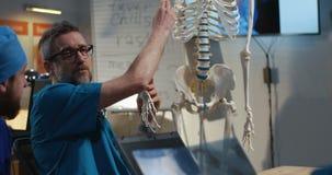 Doctors examining cervical spine x-ray. Medium shot of doctors examining cervical spine x-ray image stock video