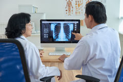 Doctors Examining Chest X-Ray. Back view of confident doctors sitting in front of computer and examining chest X-ray, one of them pointing at something on screen stock photos