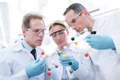 Doctors examining molecular model. Three doctors in protective glasses and lab coats examining a molecular model royalty free stock image