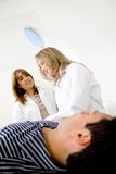 Doctors examining a patient Royalty Free Stock Image
