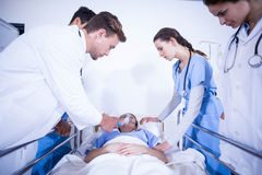 Doctors examining a patient on bed Stock Photography