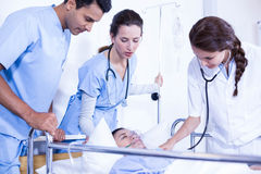 Doctors examining a patient on bed. In hospital Royalty Free Stock Photography