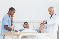 Doctors examining a patient Stock Images