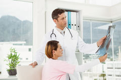 Doctors examining x-ray in medical office Stock Images