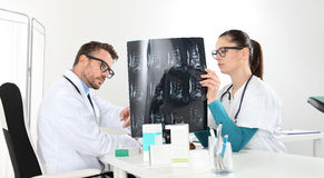 Doctors examining x-ray at office. Doctors examining x-ray in office stock photography