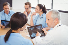 Doctors examining an x-ray report. In hospital and colleagues discussing in background Royalty Free Stock Images