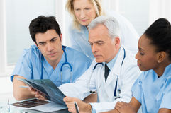 Doctors Examining X-ray Report. Team Of Experts Doctors Examining X-ray Report In Hospital royalty free stock photography