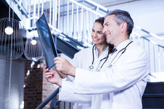 Doctors examining a x report on staircase. In hospital Stock Photography