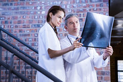 Doctors examining a x report on staircase. In hospital Stock Photos