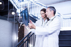 Doctors examining a x report on staircase. In hospital Royalty Free Stock Photos