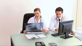 Doctors are examining a Xray file. In an office stock footage