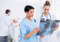 Doctors examining xray with patient in background Stock Photos