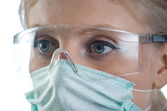 Doctors eyes. A doctor wearing a mask and eyeprotection on white background Stock Photos
