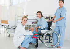 Doctors with female patient in wheelchair at hospital Stock Photo