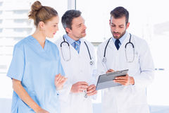 Doctors and female surgeon reading medical reports. Two male doctors and female surgeon reading medical reports at the hospital Stock Images
