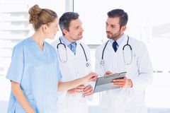 Doctors and female surgeon reading medical reports. Two male doctors and female surgeon reading medical reports at the hospital Stock Photos