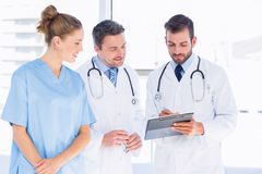 Doctors and female surgeon reading medical reports. Two male doctors and female surgeon reading medical reports at the hospital Stock Photo