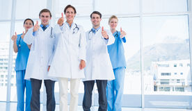 Doctors gesturing thumbs up at hospital Stock Photo