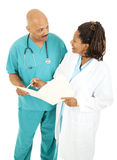 Doctors Going Over Medical Chart Stock Photography