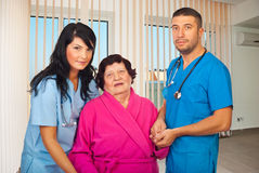 Doctors helping elderly woman patient. Two mid adults doctors holding elderly woman hands to help her to walk in a hospital room Royalty Free Stock Image