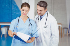 Doctors holding clipboard while examining. At hospital stock photos