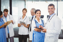 Doctors holding clipboard in hospital. Portrait of doctors holding clipboard and colleagues standing and discussing in hospital Stock Image