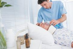 Doctors holding patients oxygen mask Stock Photos