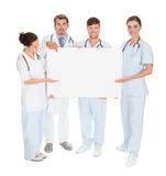 Doctors holding placard. Group Of Doctors Holding Blank Placard Over White Background Stock Photography