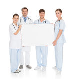 Doctors Holding Placard. Group Of Doctors Holding Blank Placard Over White Background Royalty Free Stock Photos