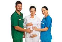 Doctors holding pregnant woman tummy Royalty Free Stock Photo