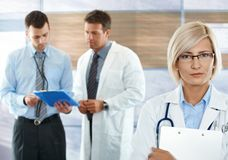 Doctors on hospital corridor. Healthcare workers on hospital corridor female doctor in front looking at camera royalty free stock image