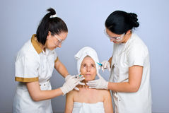 Doctors  injecting botox to senior woman Stock Photo