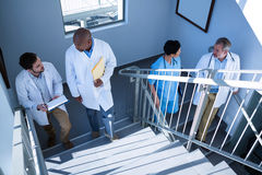 Doctors interacting with each other while climbing stairs Stock Photography