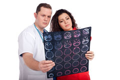 Doctors interpreting computed tomography (CT). Young couple of handsome men doctor and pretty nurse in white and tangerine tango uniforms looking at a computed Royalty Free Stock Photos