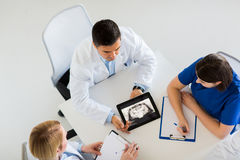 Doctors with jaw x-ray on tablet pc at clinic. Medicine, healthcare and oral surgery concept - group of doctors or surgeons discussing jaw x-ray on tablet pc royalty free stock photo